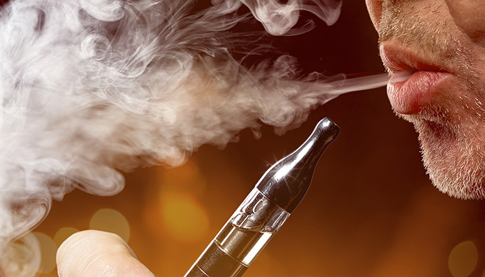 Vaping Inhaling and exhaling the vapor from electronic cigarette